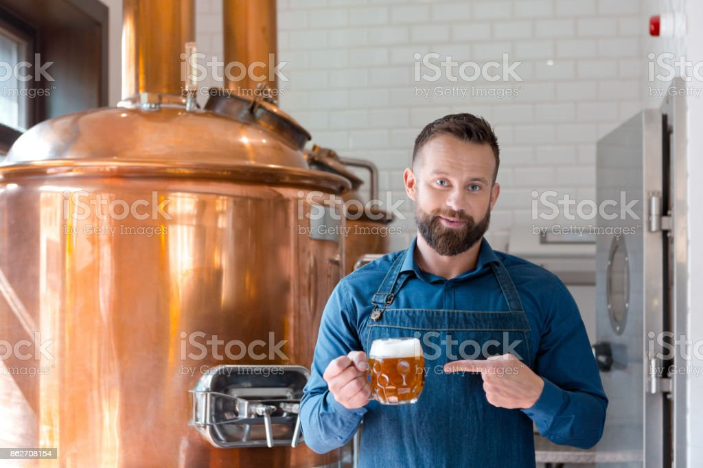 The master brewer holding beer mug in his micro brewery Happy master brewer standing in front of copper vat and holding beer mug in his micro brewery. Adult Stock Photo