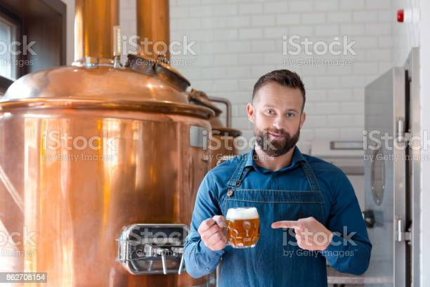The Master Brewer Holding Beer Mug In His Micro Brewery Stock Photo - Download Image Now