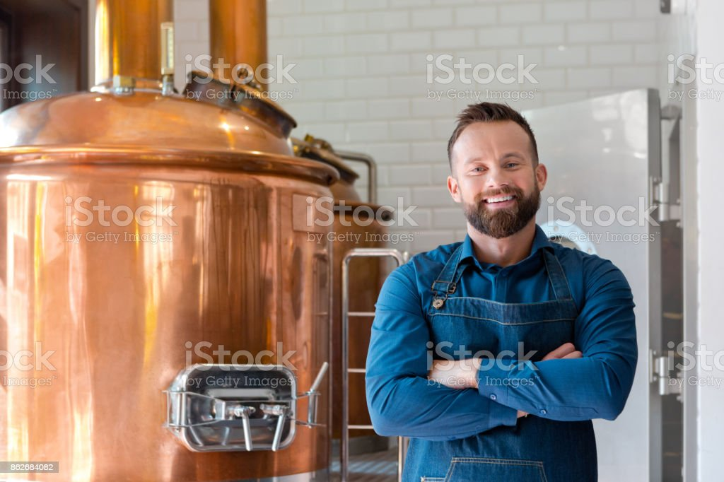 The master brewer in his micro brewery Happy master brewer standing in front of copper vat in his micro brewery, smiling at the camera. Adult Stock Photo