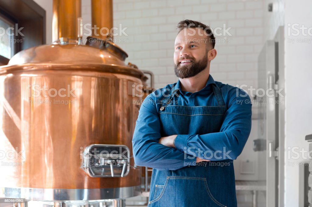 The master brewer in his micro brewery Happy master brewer standing with arms crossed in front of copper vat in his micro brewery. Adult Stock Photo