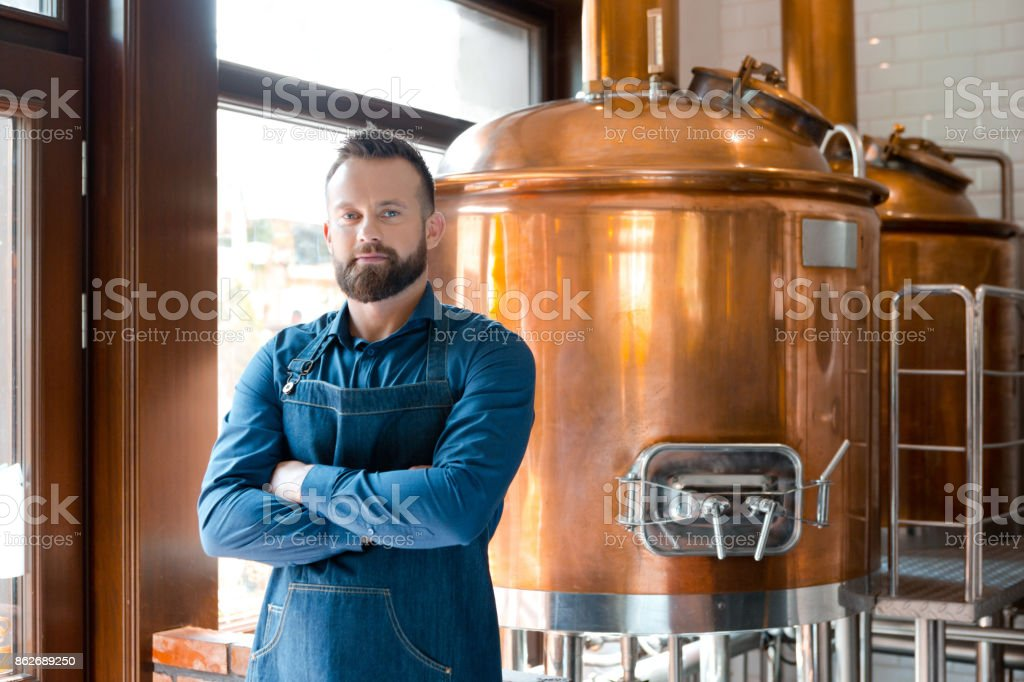 The master brewer in his micro brewery Happy master brewer standing with arms crossed in front of copper vat in his micro brewery, looking at the camera. Adult Stock Photo