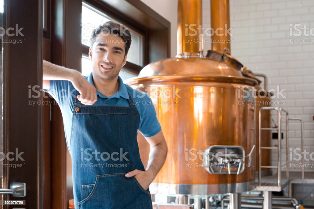 The master brewer in micro brewery Happy master brewer standing in front to copper vat and smiling at the camera. Adult Stock Photo