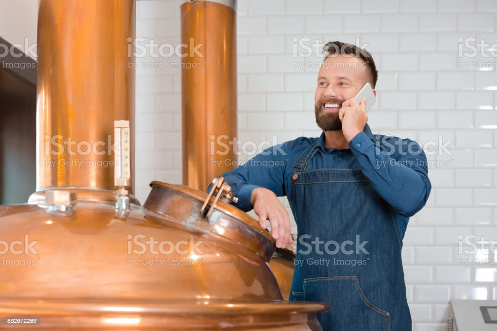 The master brewer talking on phone in his micro brewery Happy master brewer standing next to copper vat and talking on phone in his micro brewery. Adult Stock Photo