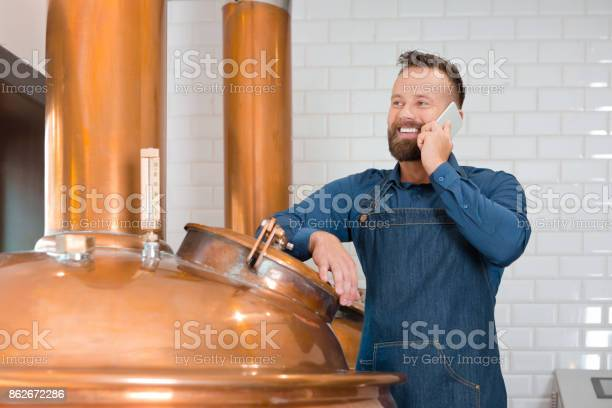 The Master Brewer Talking On Phone In His Micro Brewery Stock Photo - Download Image Now