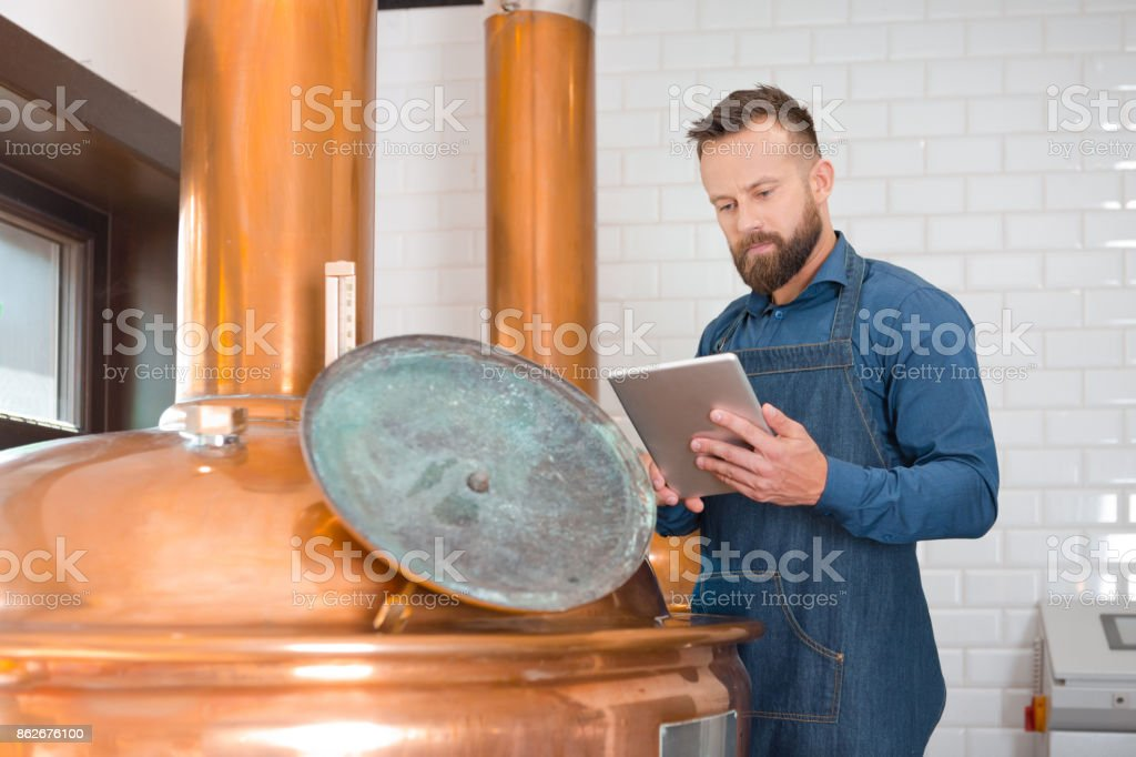The master brewer using a digital tablet in his micro brewery Master brewer standing next to copper vat and using a digital tablet in his micro brewery. Adult Stock Photo