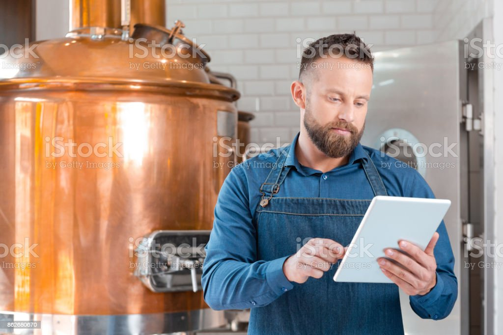 The master brewer using a digital tablet in his micro brewery Master brewer standing in front to copper vat and using a digital tablet in his micro brewery. Adult Stock Photo