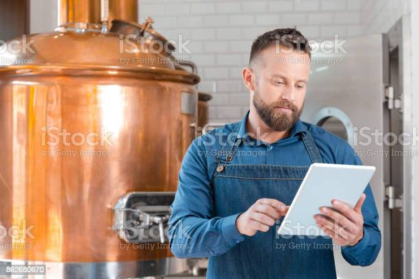 The Master Brewer Using A Digital Tablet In His Micro Brewery Stock Photo - Download Image Now