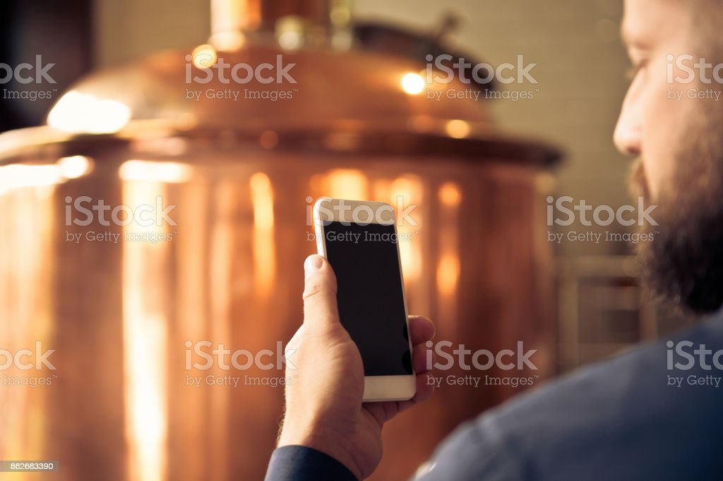 The master brewer using smart phone in his microbrewery The master brewer standing in front of copper vat and using smart phone in his micro brewery. Adult Stock Photo