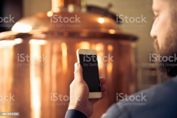 The Master Brewer Using Smart Phone In His Microbrewery Stock Photo - Download Image Now