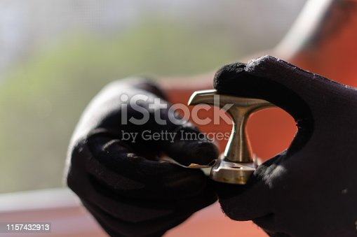 The master in black gloves recovers, polishes the brass copper window handle.Selective focus.
