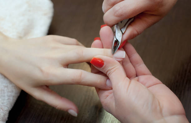 the master of the manicure cuts the cuticles on the hands in the beauty salon. - deposition stock pictures, royalty-free photos & images