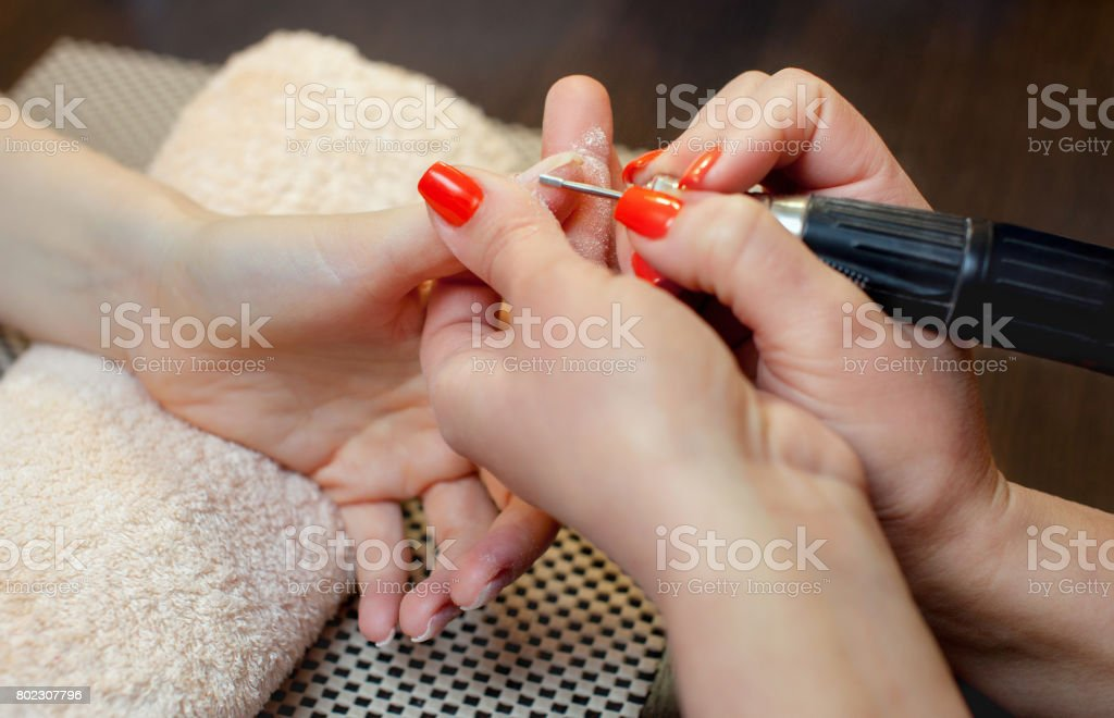 The master of the manicure saws and attaches a nail shape during the procedure of nail extensions with gel stock photo