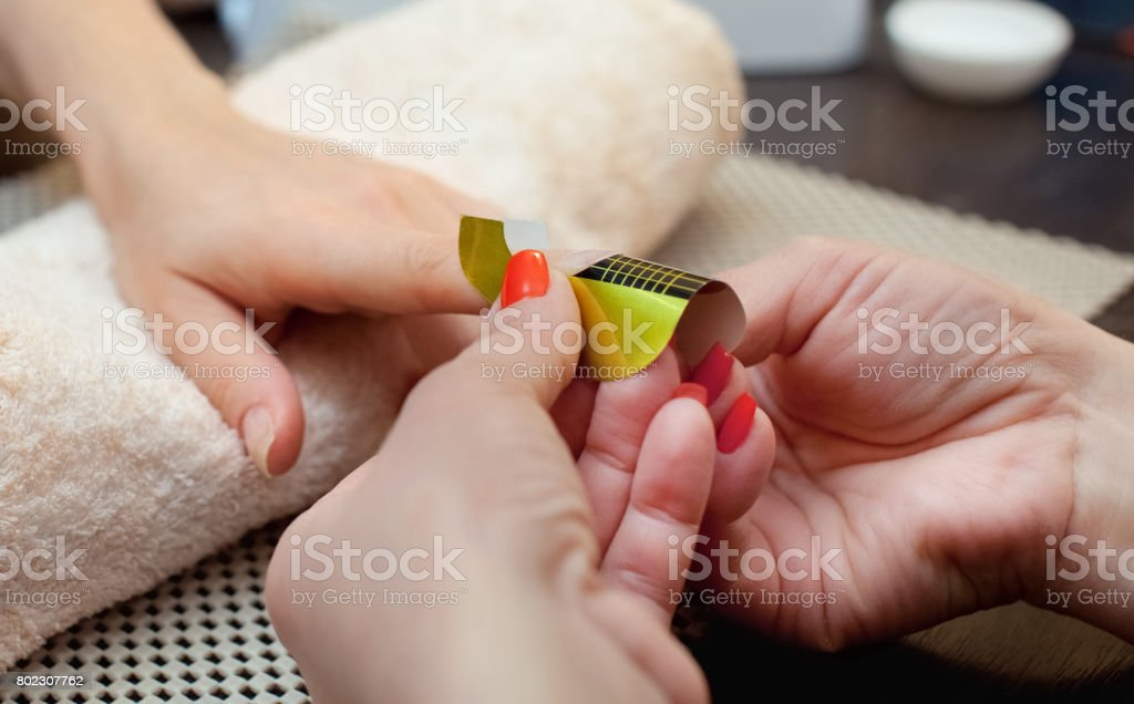 The master of the nail polish puts a fixative on the finger before making the nails gel stock photo