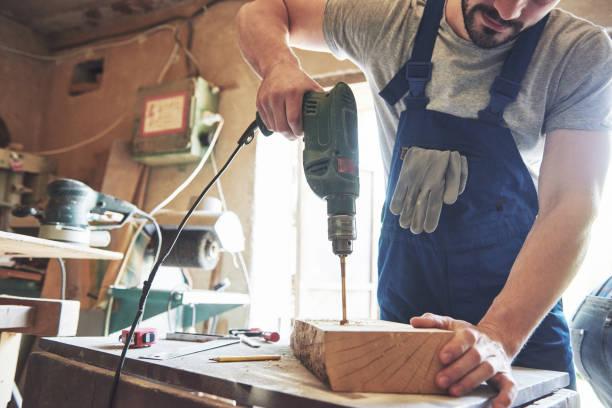 Der Meister arbeitet in einem Atelier und bohrt ein Loch in ein Holzbrett. – Foto