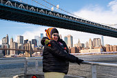 The mature, 45 years old Caucasian-white woman enjoying a trip on the ferry on the East River along Manhattan in the cold sunny windy day. New York City, USA