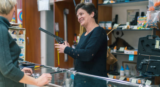 The mature blonde woman buying the revolver in the small gun store The mature blonde woman buying the revolver in the small gun store gun shop stock pictures, royalty-free photos & images