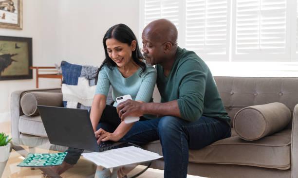 Das reife Paar sitzt zusammen auf einer Couch und nutzt einen PC-Laptop für Online-Shopping oder Videoanruf über das Internet. – Foto