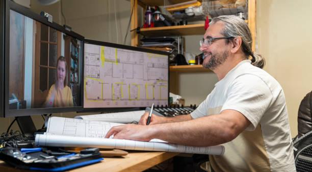 Der reife Mann arbeitet im HomeOffice mit Architekturzeichnungen und hat eine Videokonferenz mit seiner Kollegin - Mitarbeiterin, einer Frau mittleren Alters. – Foto