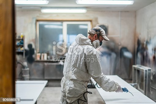 The mature man, manual worker, wearing the protective mask and coveralls, cleaning surfaces for painting with the compressed air gun at the small furniture manufacture
