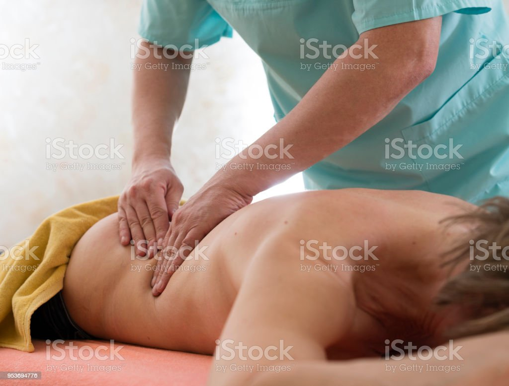 The mature man, massagist, doing medical massage of the back to the mature 50-years-old woman stock photo