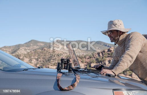 The mature man, the traveler, working with the laptop on the car hood outdoor, in the front of the mountains of Colorado, USA.
