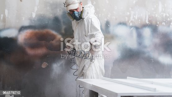 The mature man wearing protective mask and coveralls painting the furniture's details with the spray gun at the small manufacture