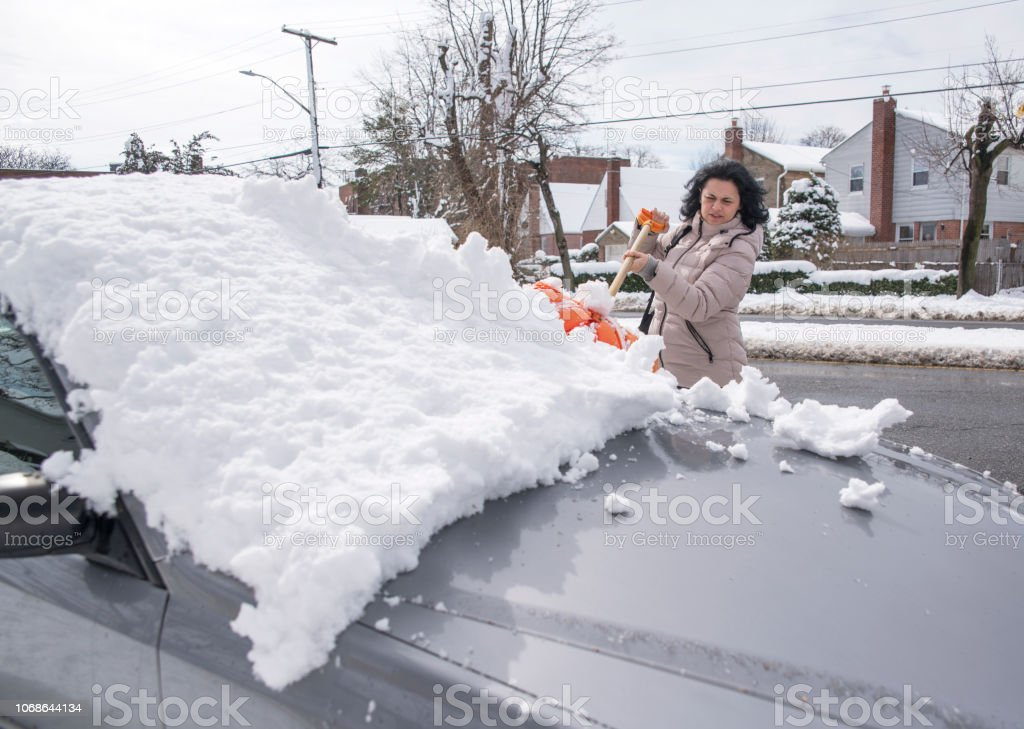The mature woman cleaning the car from the snow after winter storm stock photo