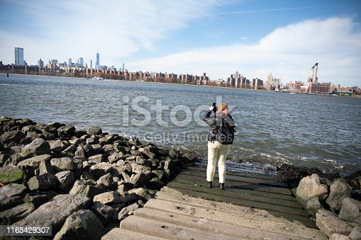 The mature woman, tourist, in Brooklyn, at the East River Waterfront in front of Manhattan