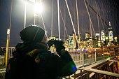 The mature 45-years-old woman, the tourist walking and taking pictures with a smartphone on Brooklyn Bridge in the night