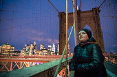 The mature 45-years-old woman, the tourist walking on Brooklyn Bridge in the night