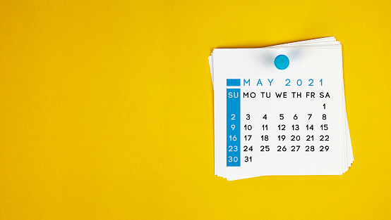 The May 2021 calendar is pinned on a yellow background. Horizontal composition with copy space.