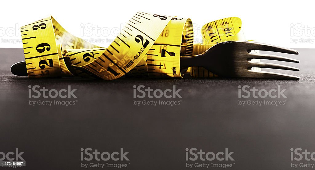 The measurements depend on your diet: measuring tape and fork royalty-free stock photo