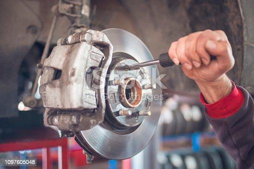 The mechanic is repairing the brake wheels.