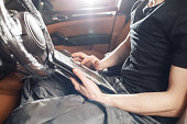 istock The mechanic sitting in the car carries out diagnostics of electronics 901101634