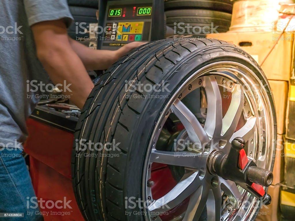 The mechanic using computerize wheel balancer to balance the wheel. Seletive focused stock photo