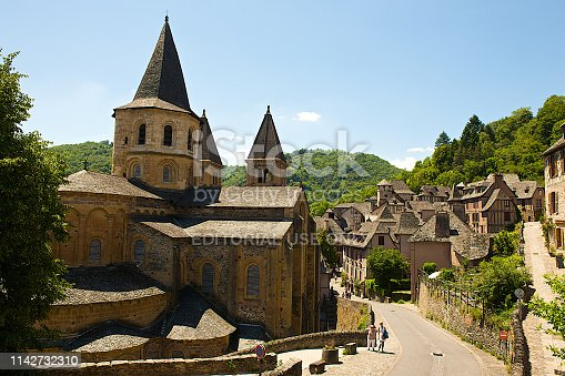 Conques, France-06 14 2014:People walking in the street of the medieval village of Conques, and admiring the Sainte-Foy Abbey-Church, located in Aveyron département, France.The Abbey Church of Saint Foy was added to the UNESCO World Heritage Sites in 1998, as part of the World Heritage Sites of the Routes of Santiago de Compostela in France.
