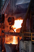 The melting metal is pouring to big melting pot in the industrial foundry plant. Metals are cast into shapes by melting them into a liquid, pouring the metal into a mold.