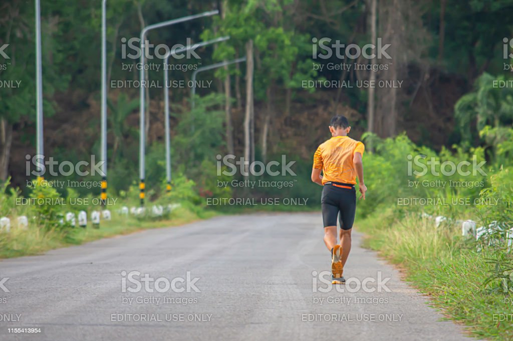 The men are running on the road Background light poles and trees at...