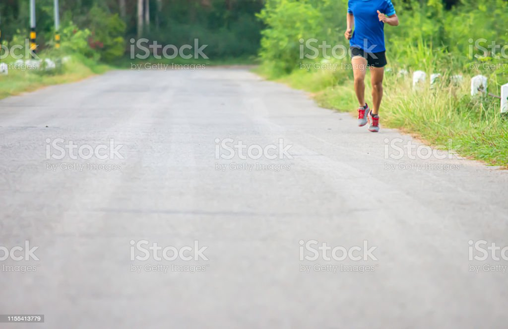 The men are running on the road Background light poles and trees.