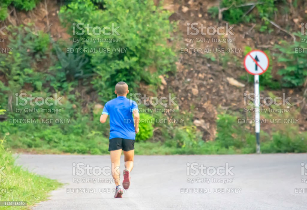 The men are running on the road Background trees and Traffic signs...