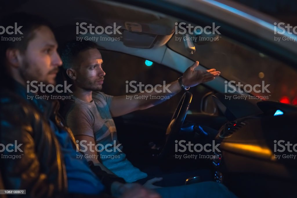 The men sit and gesture inside the car on the road. Evening night time