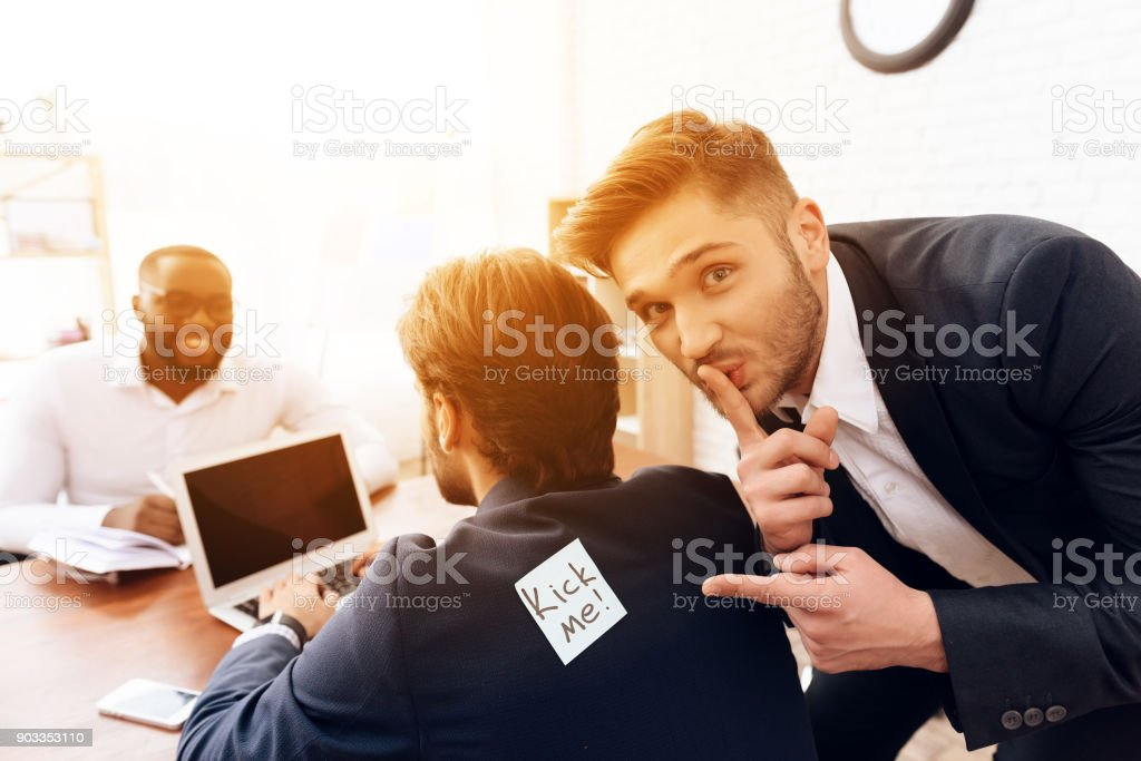 The men stuck a sticker on the back of another man. stock photo
