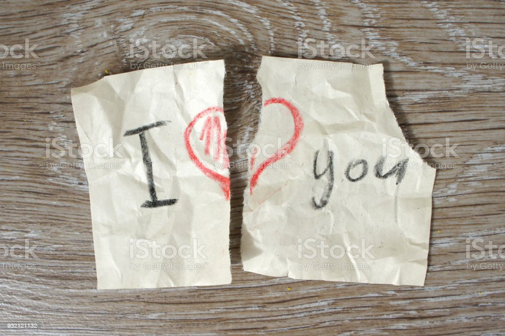 The message 'I love you' with a heart torn in half. Broken note on paper with a pencil on wooden background. Flat lay stock photo
