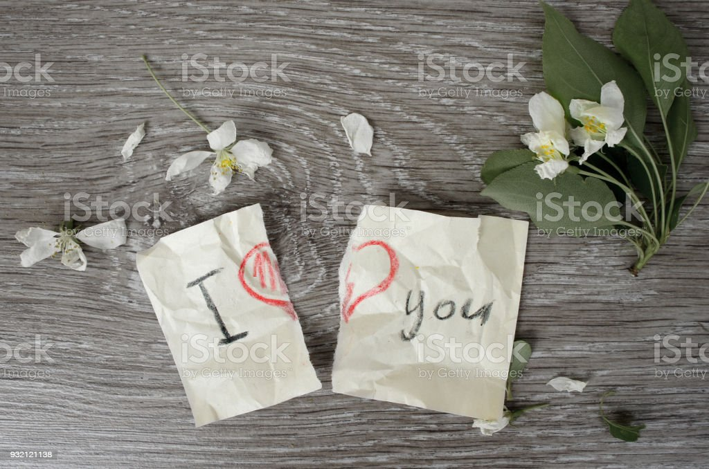 The message 'I love you' with a heart torn in half. Broken note on paper with a pencil on wooden background with flowers Apple tree. Flat lay. stock photo