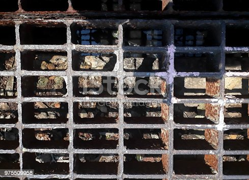 Sewer next to the village, rustic artsy abstract background, sewer cover