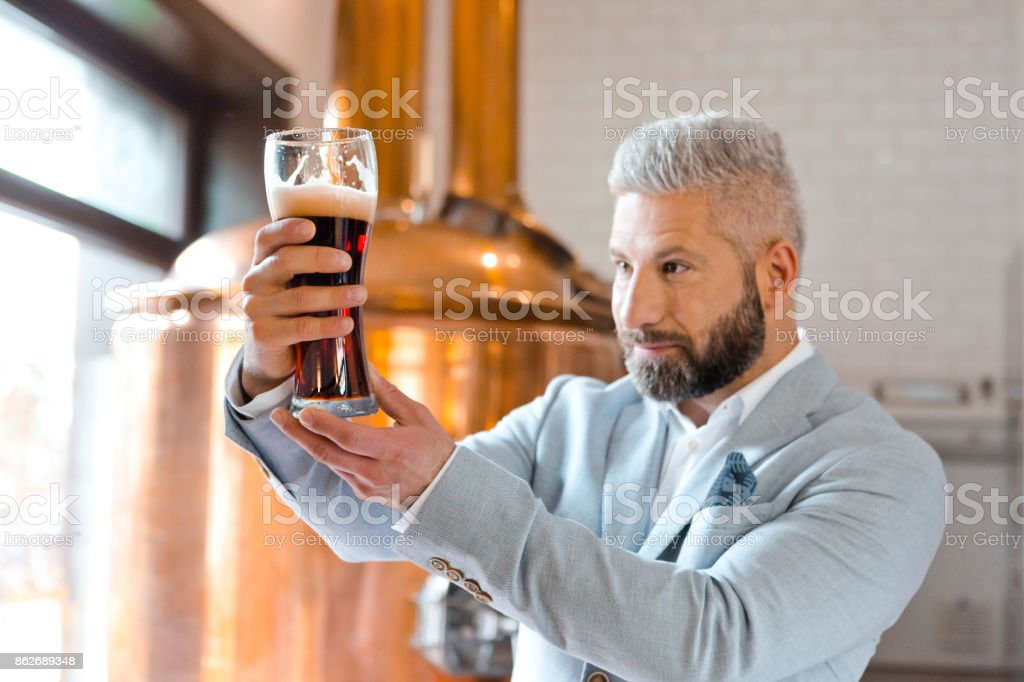 The microbrewery owner chceking quality of beer in his pub Happy microbrewery owner standing in front to copper vat and holding beer glass, checking quality. Adult Stock Photo