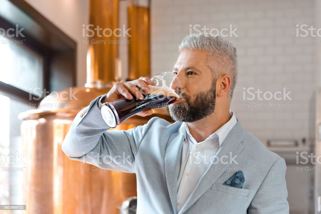 The microbrewery owner drinking ale beer in his pub The microbrewery owner standing in front to copper vat and drinking ale beer. Adult Stock Photo