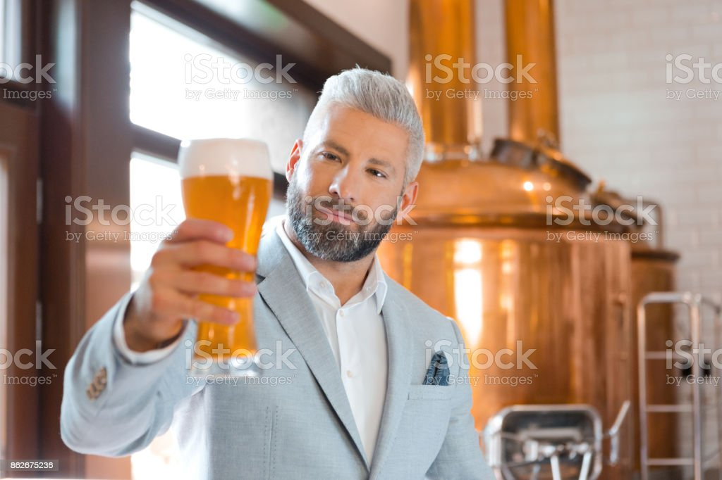 The microbrewery owner holding a beer glass in his pub The microbrewery owner standing in front to copper vat and holding beer glass, checking quality. Adult Stock Photo