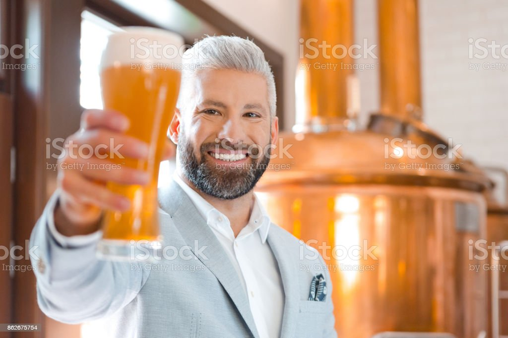 The microbrewery owner holding a beer glass in his pub The microbrewery owner standing in front to copper vat and holding beer glass, smiling at the camera. Adult Stock Photo