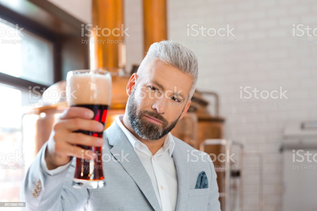 The microbrewery owner holding a beer glass in pub Confident microbrewery owner standing in front to copper vat and holding beer glass. Adult Stock Photo